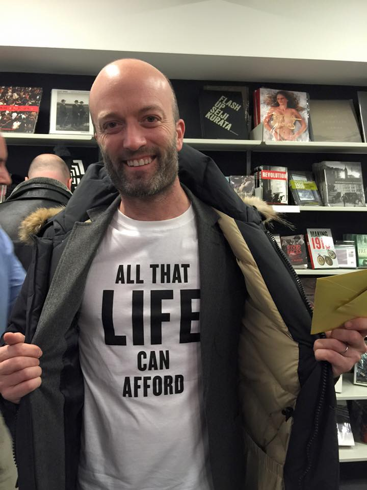 Matt Stuart at his book launch wearing shameless self promotional T-Shirt of his new books title All That Life Can Afford